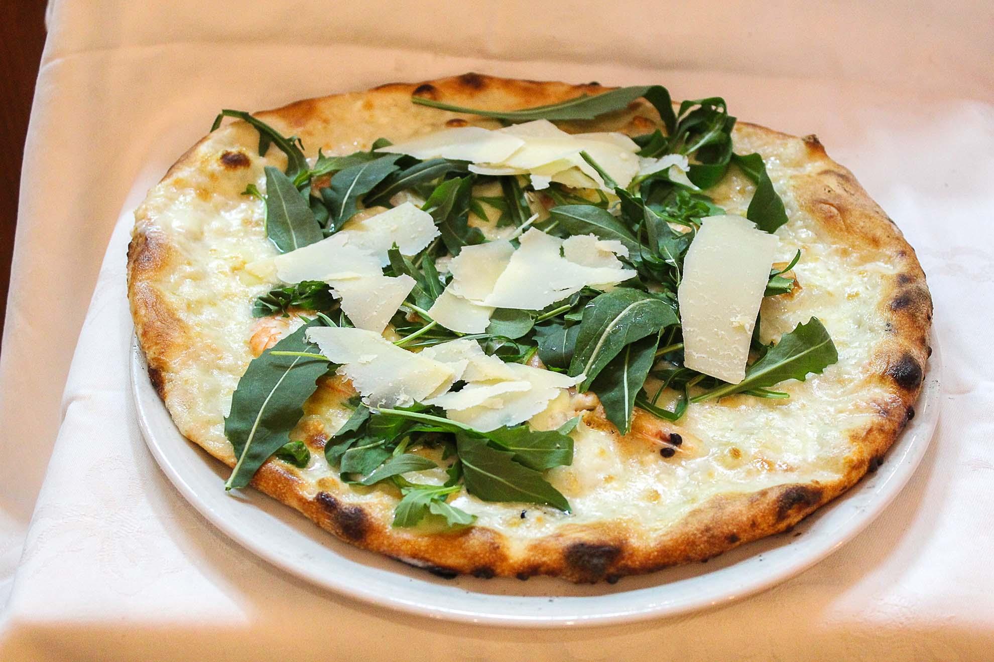 Pizza con mozzarella, gamberetti, rucola e scaglie