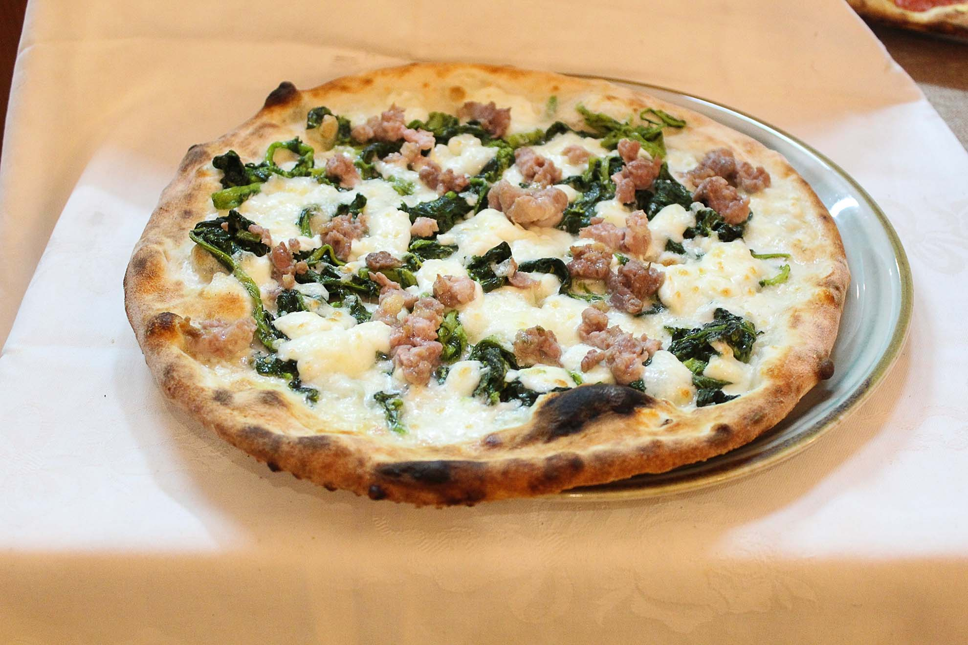 Pizza con mozzarella, broccoli e salsiccia